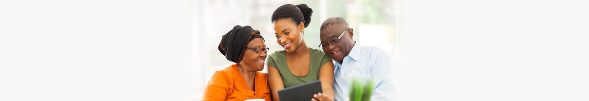 Cheerful african family at home using tablet pc